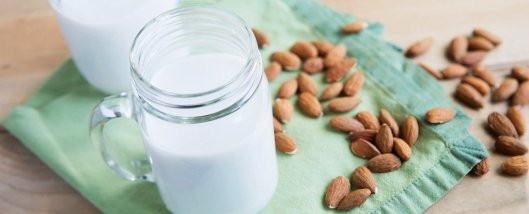 glass of almond milk with almonds strewn about